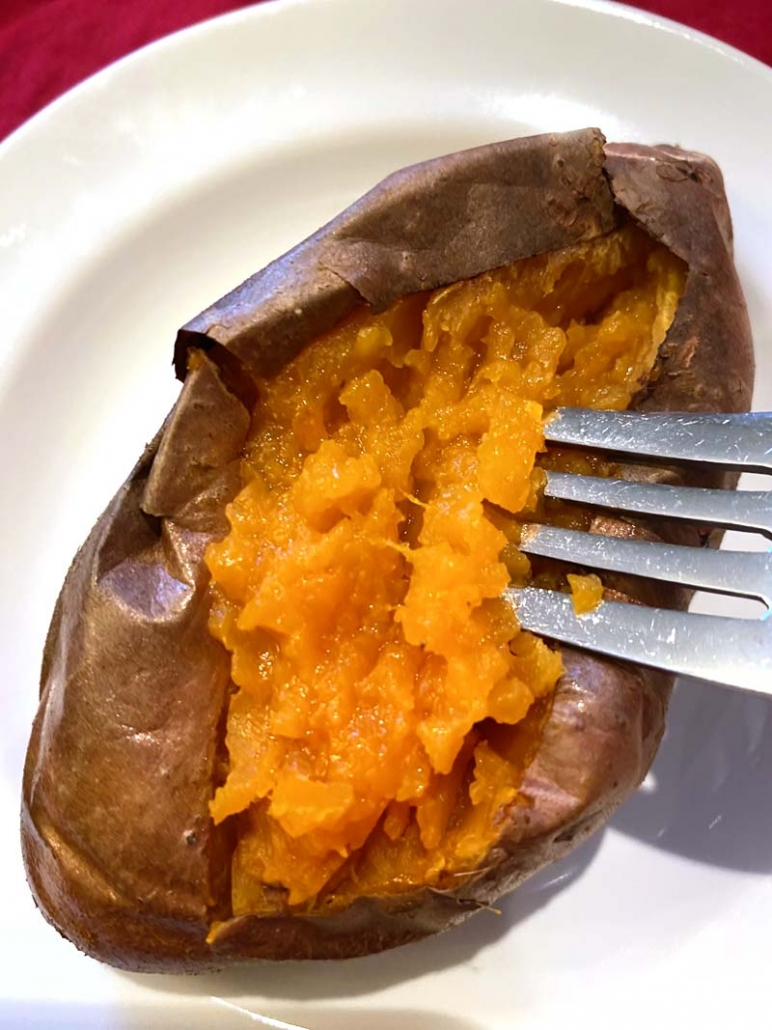 eating a sweet potato with a fork