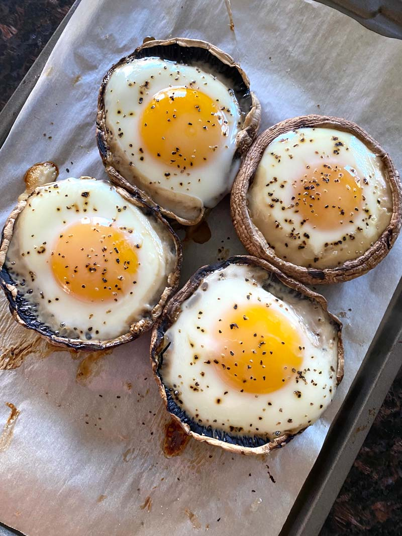 Four baked eggs in mushrooms ready to serve