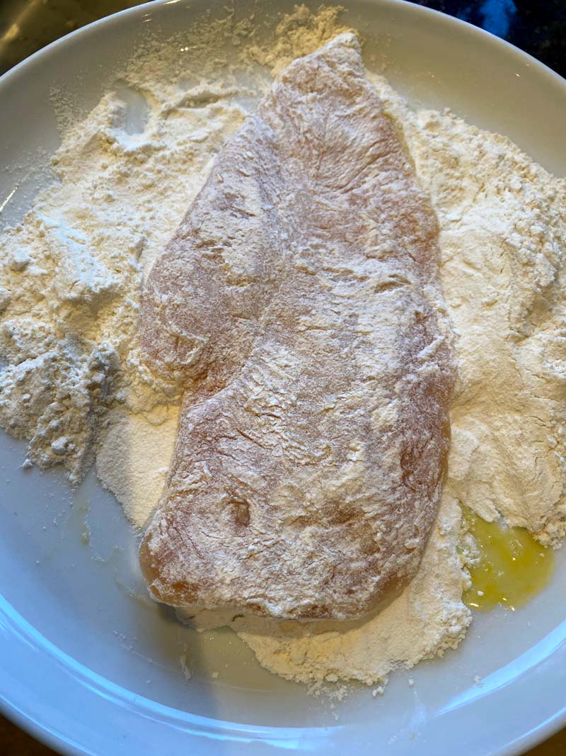 Chicken breast being covered with flour