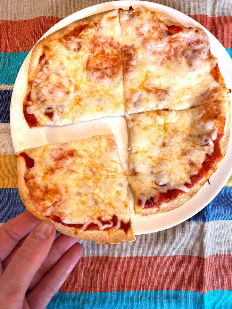tortilla pizza on a plate with hand taking a slice of pizza
