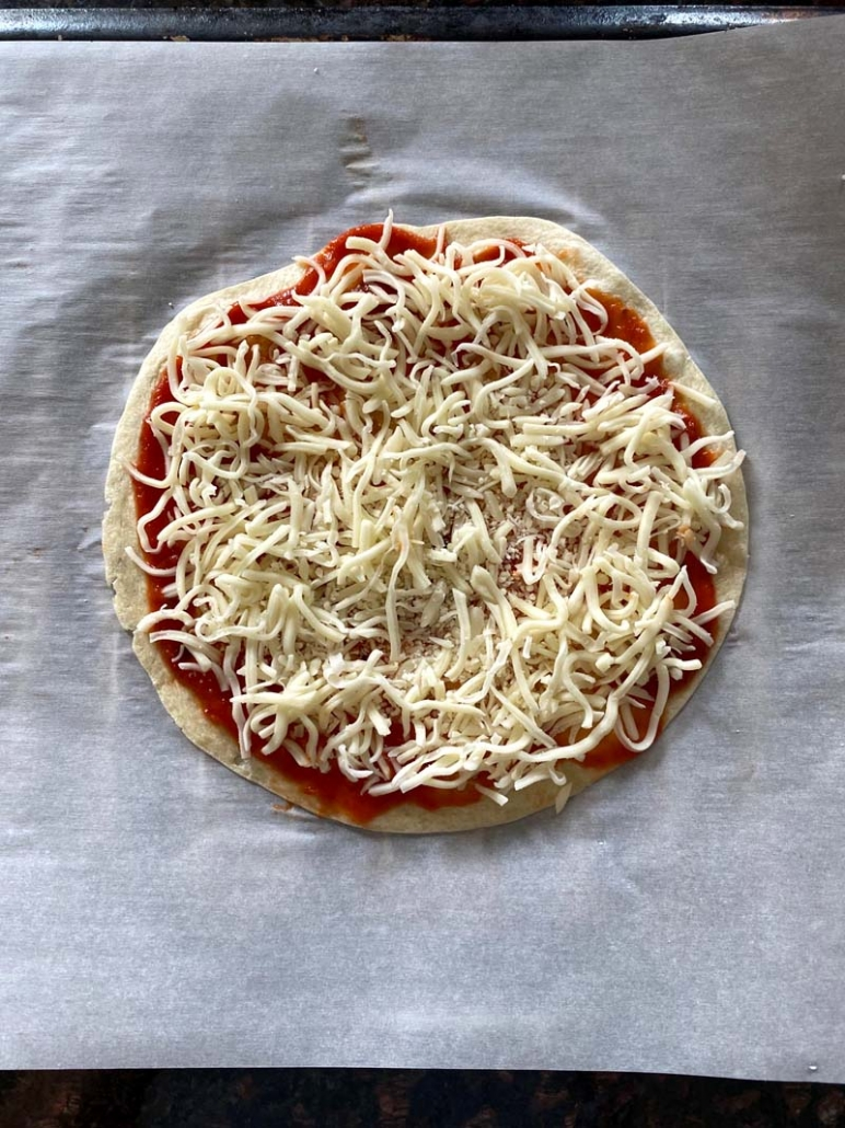 tortilla pizza spread with tomato sauce and sprinkled with shredded cheese