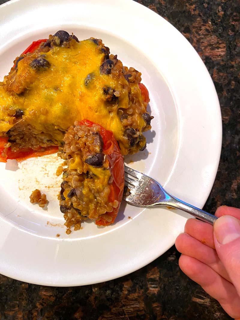 A vegetarian stuffed pepper being eaten with a fork