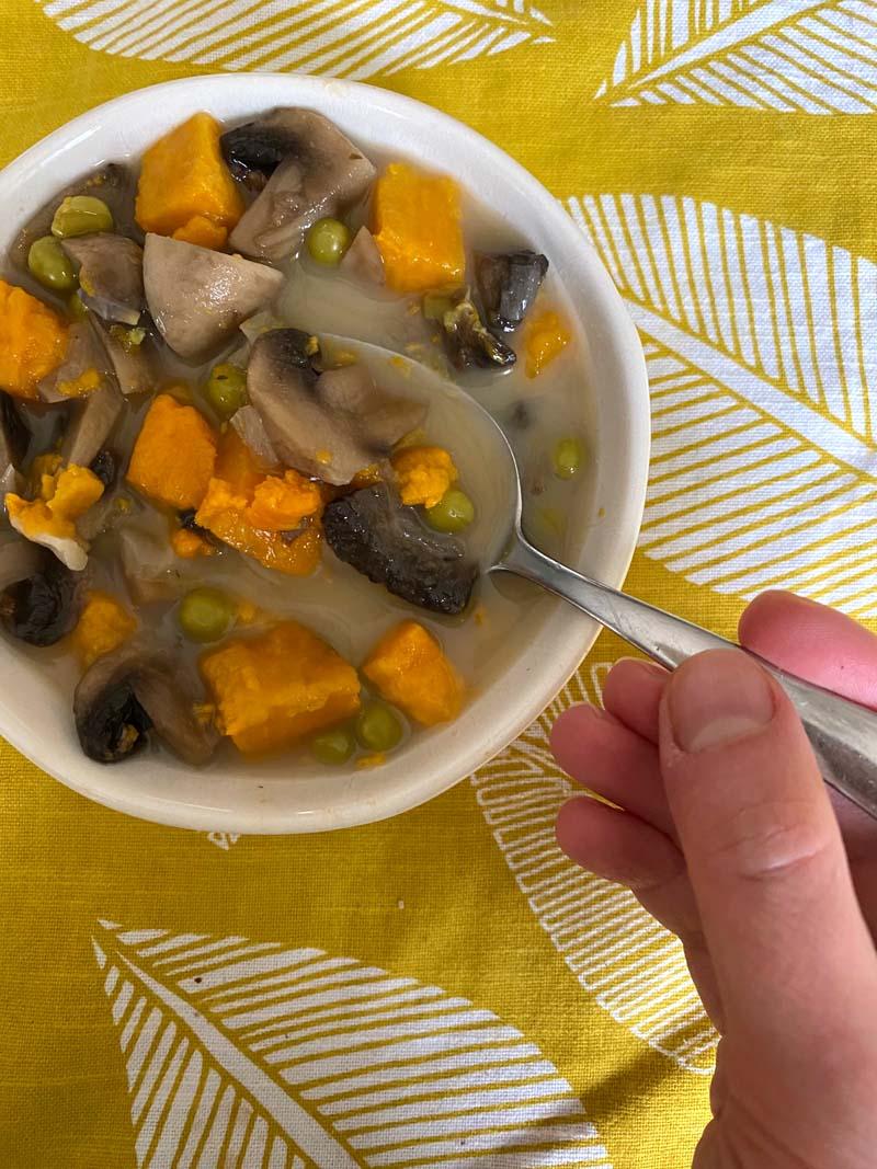 Easting the mushroom sweet potato soup with a spoon