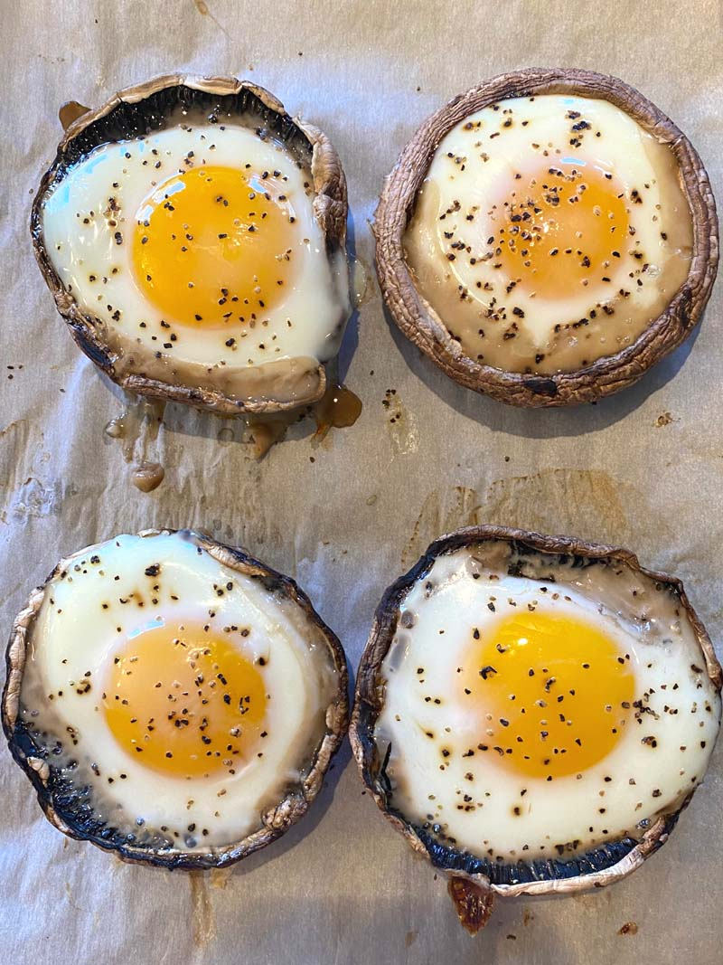 Four baked portobellos with eggs on parchment paper