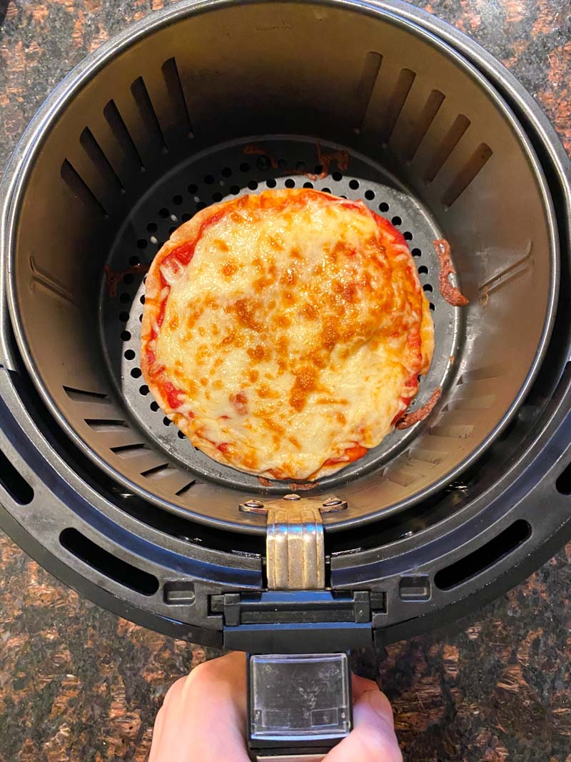 The cooked pita pizza in the air fryer basket
