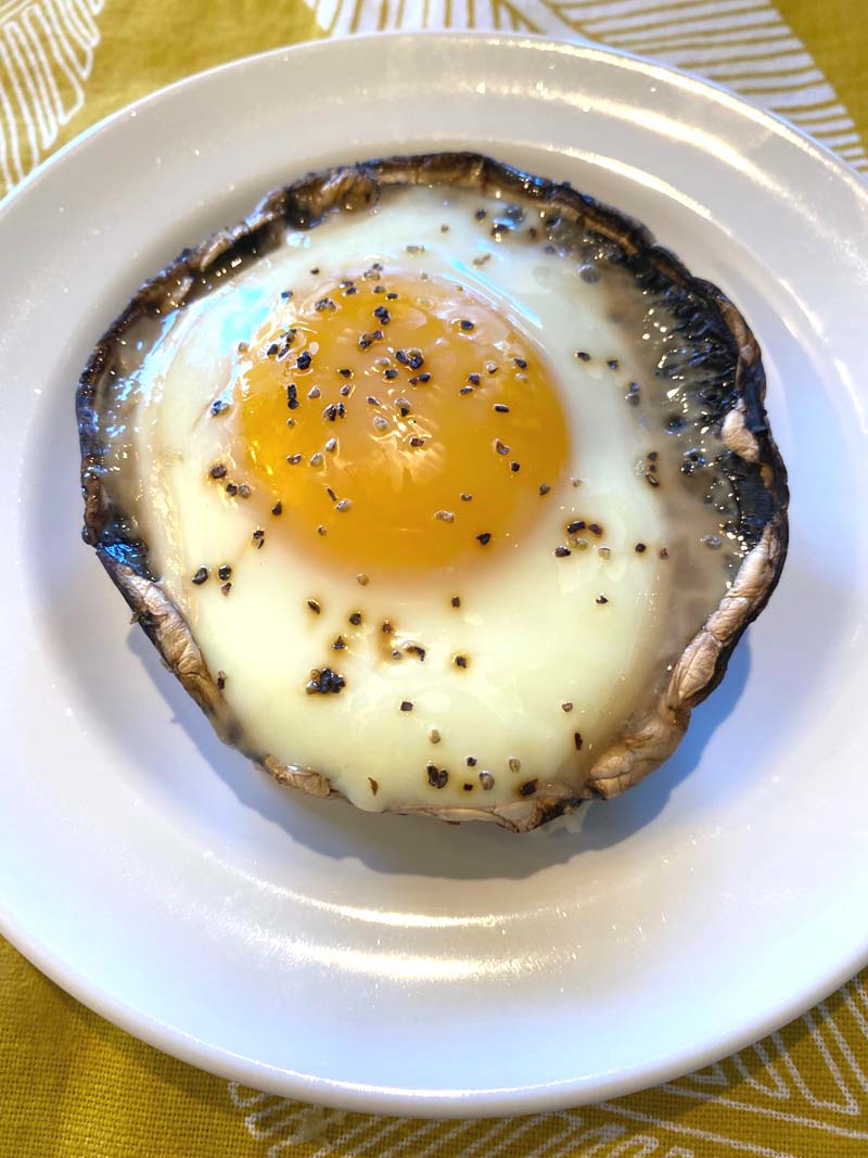 A portobello with baked egg on a white plate