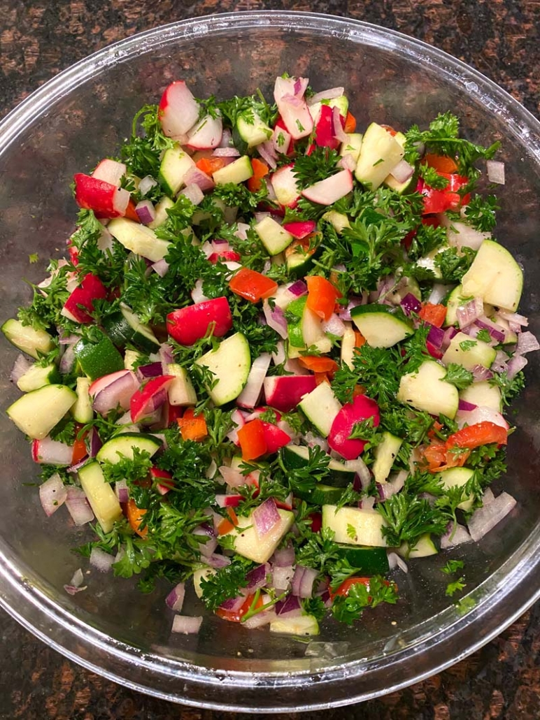 healthy salad with raw zucchini radishes bell peppers onions parsley
