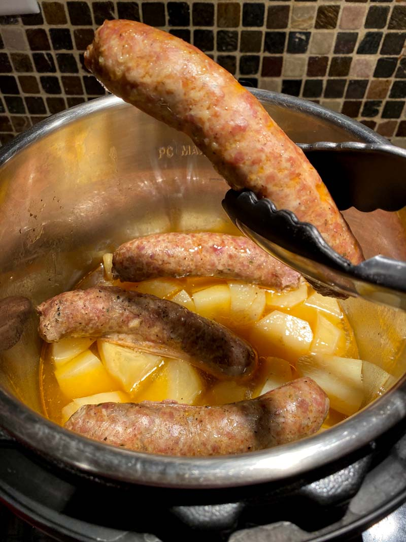 Lifting a sausage out of the instant pot with some tongs