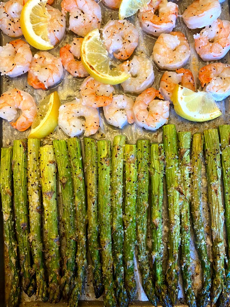 close up of asparagus and shrimp on a baking sheet