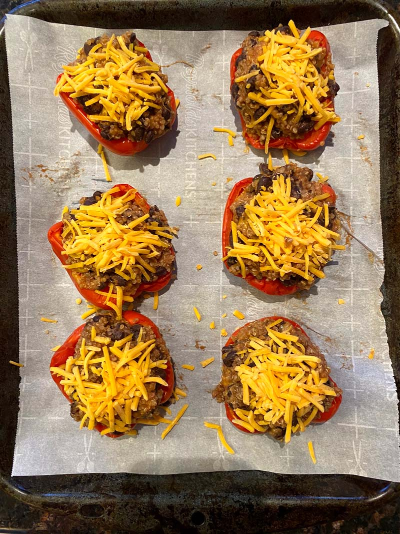 six stuffed bell peppers topped with cheese before baking