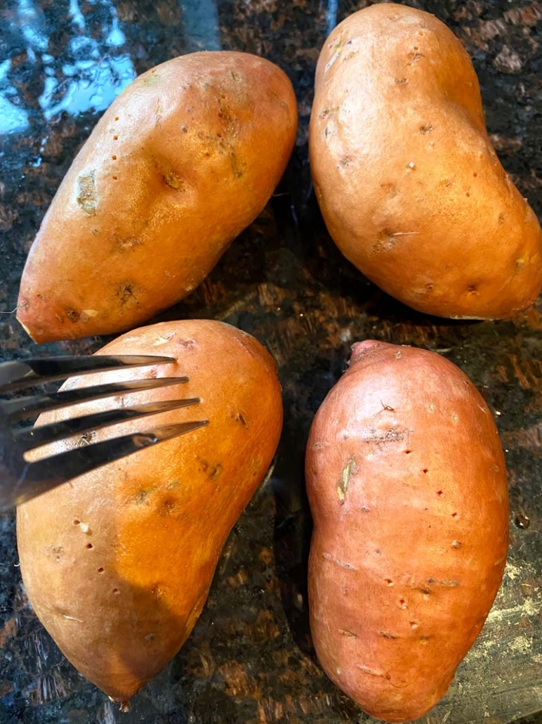 Piercing raw sweet potatoes with a fork