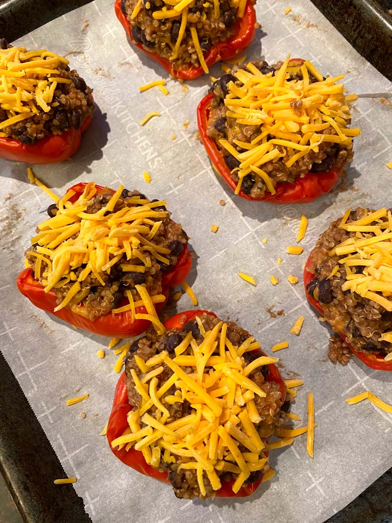 Stuffed peppers topped with cheese on a baking sheet