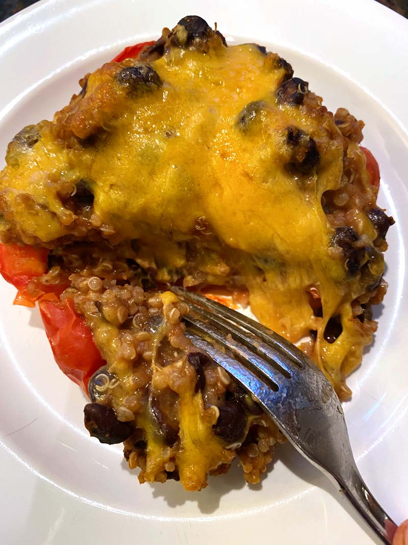 Clos eup of a fork cutting into a baked vegetarian stuffed pepper