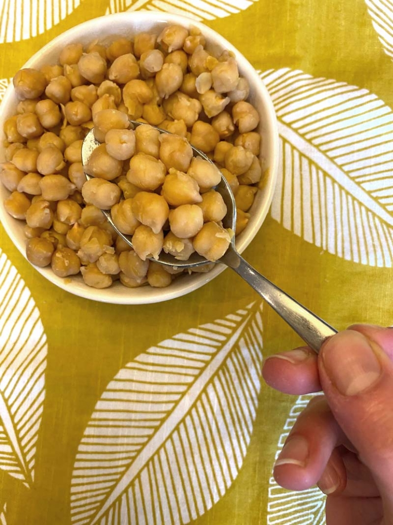 using a spoon to eat chickpeas from white bowl