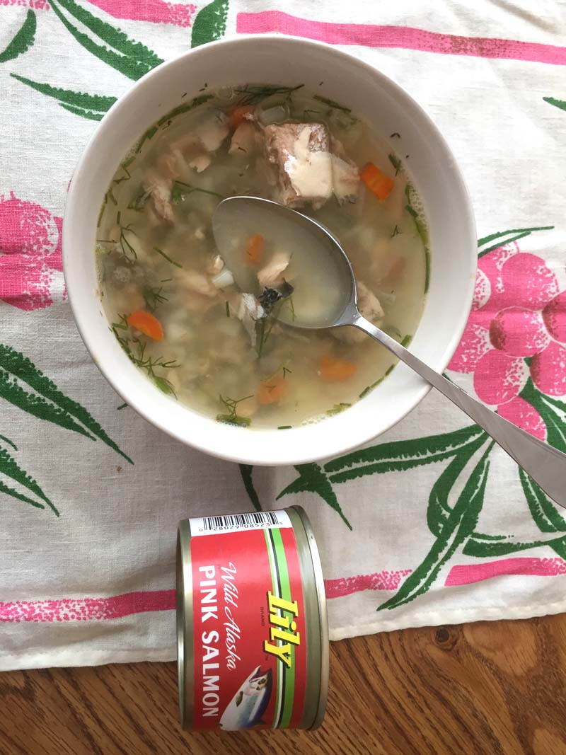 The soup in a white bowl next to the canned salmon