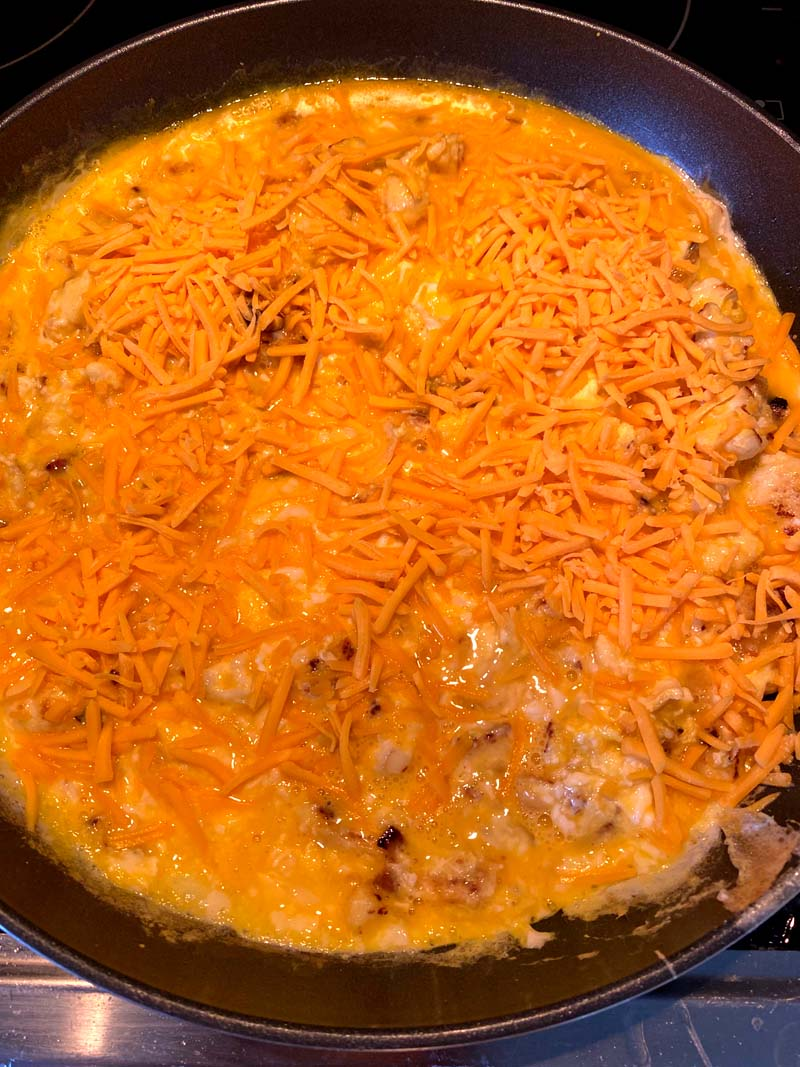 eggs and shredded cheese added to the skillet