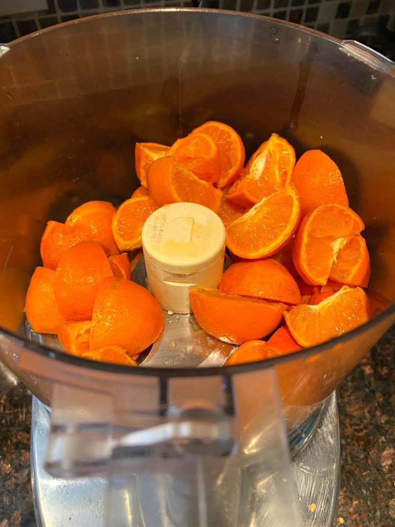 adding oranges to food processor