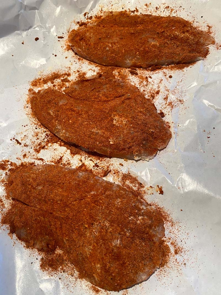 adding blackened seasoning to tilapia