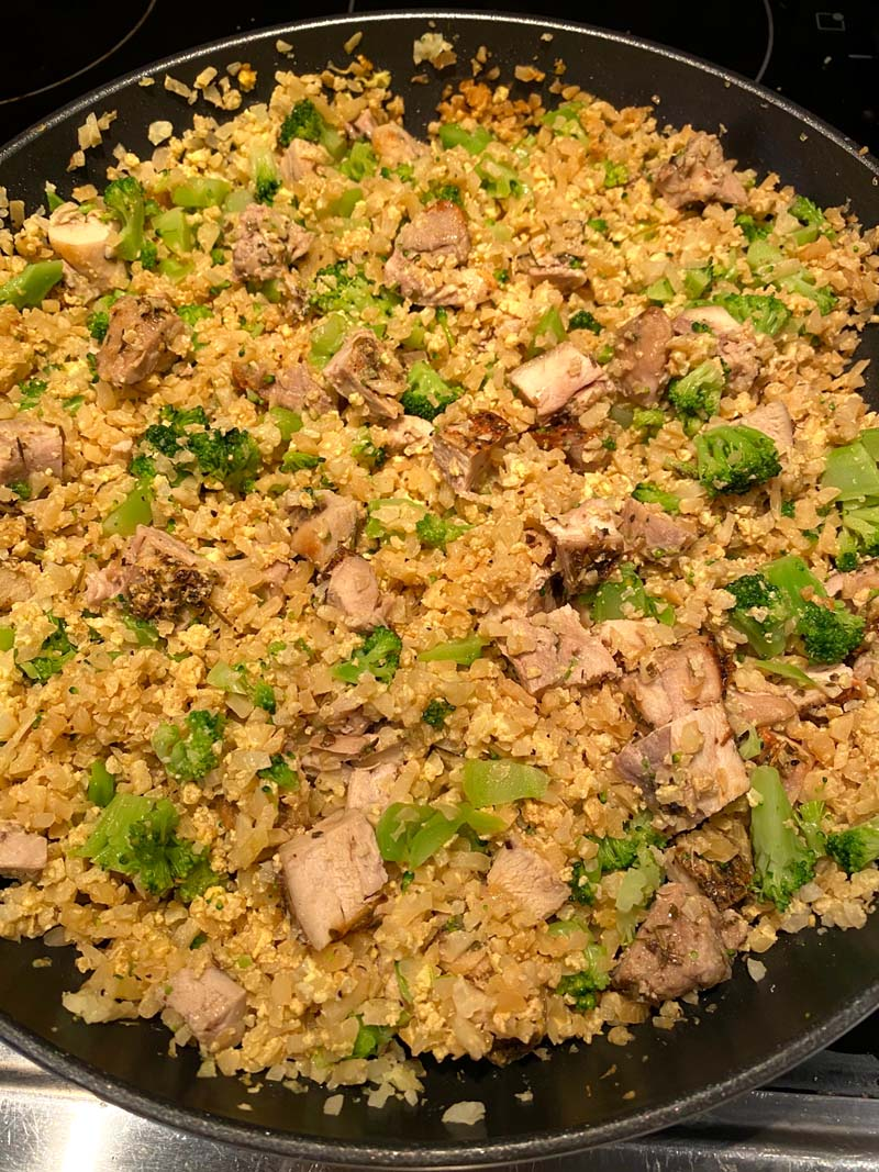 pan full of cauliflower fried rice with chicken and broccoli