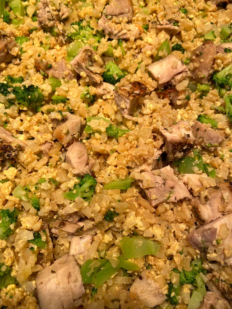 Close up of cauliflower fried rice with chicken and broccoli