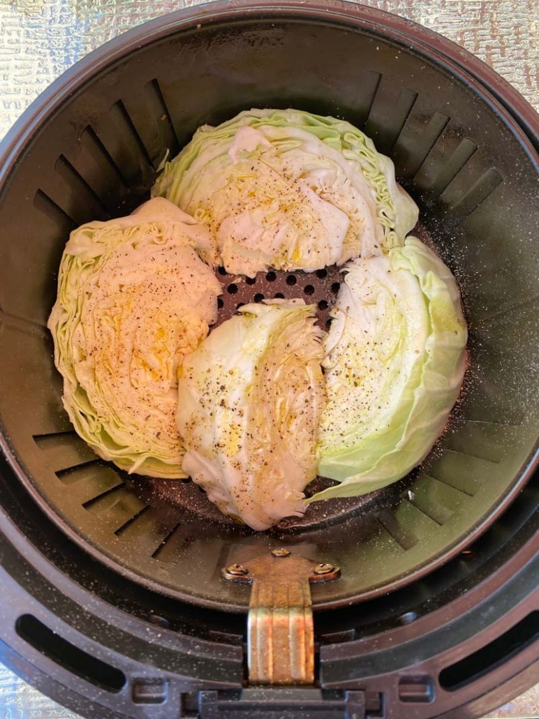 adding olive oil and seasoning to uncooked cabbage wedges