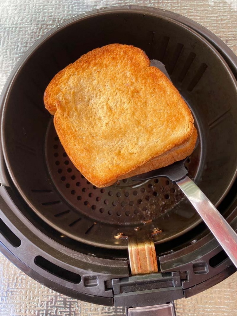 using a spatula to remove grilled cheese from air fryer basket