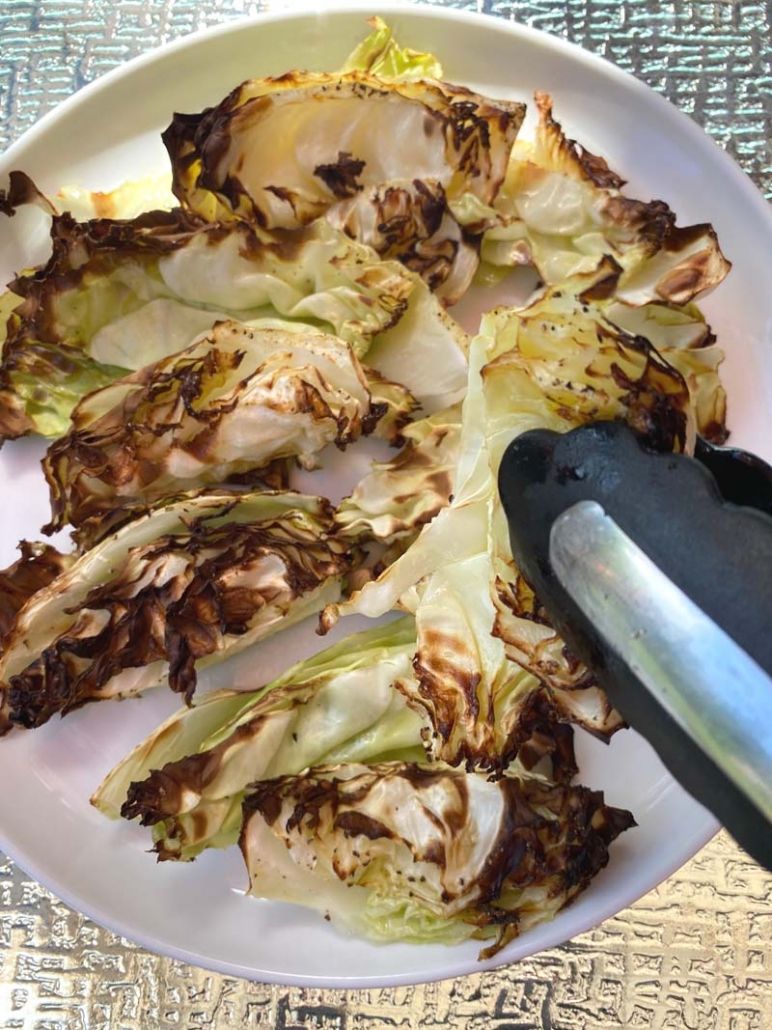 Serving air fried cabbage wedges with tongs