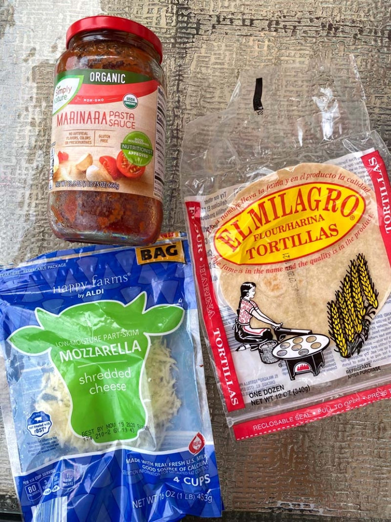ingredients to make tortilla pizza: marinara sauce, shredded cheese and flour tortillas