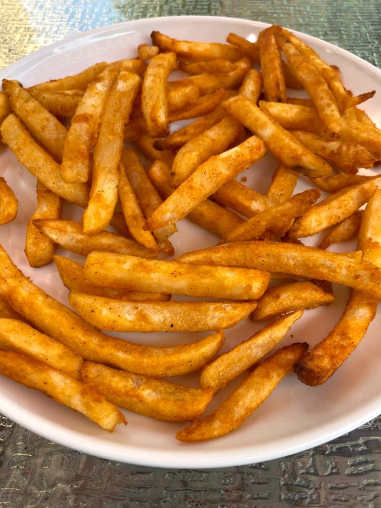 cooked french fries on a white plate