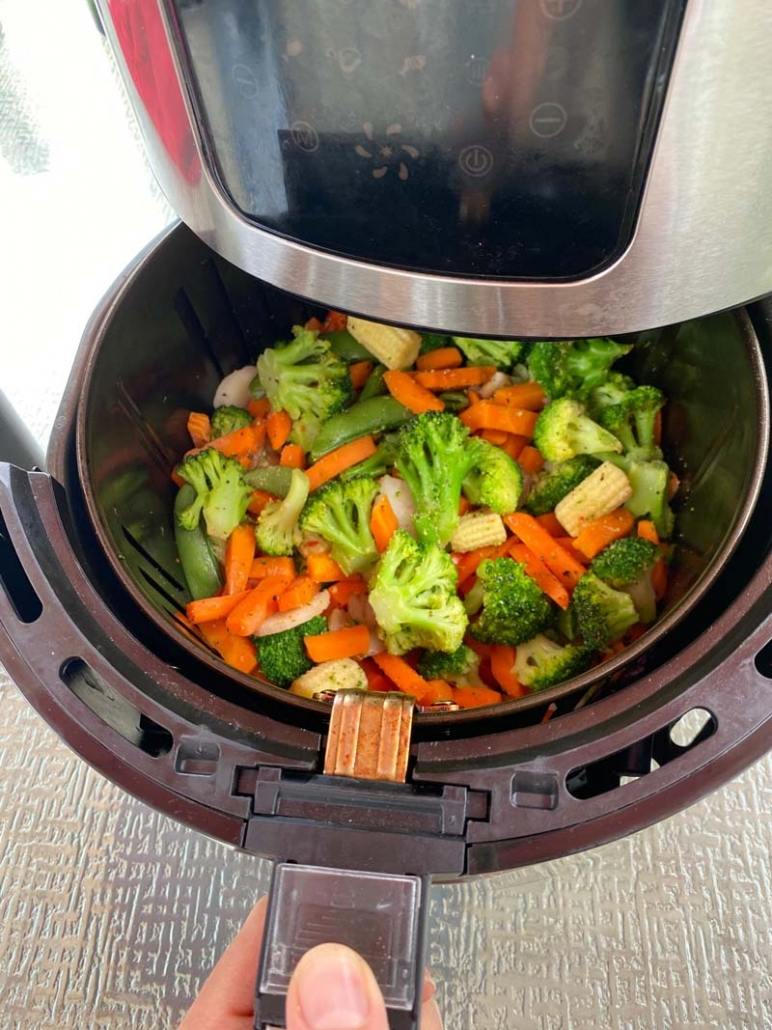 Pulling out the basket from the air fryer with mixed vegetables inside