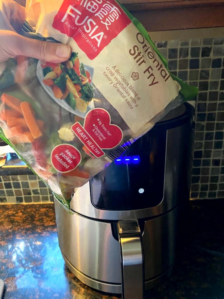 A bag of oriental stir fry mixed vegetables being held in front of an air fryer