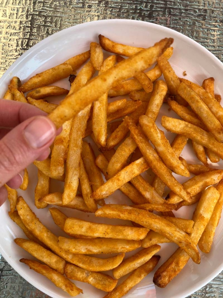 eating crispy french fries off a white plate