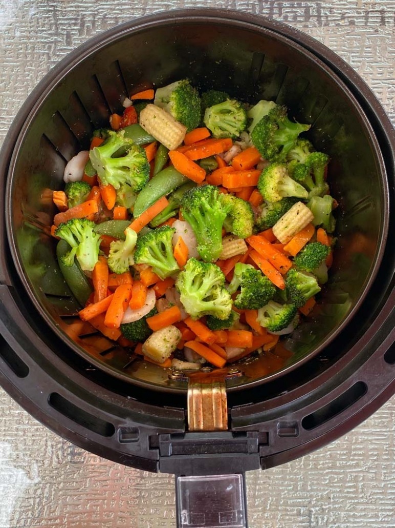 An air fryer basket with cooked mixed vegetables inside