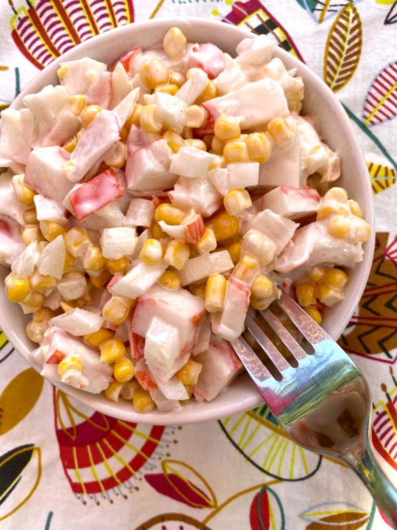 A fork in a bowl of imitation crab and canned corn salad