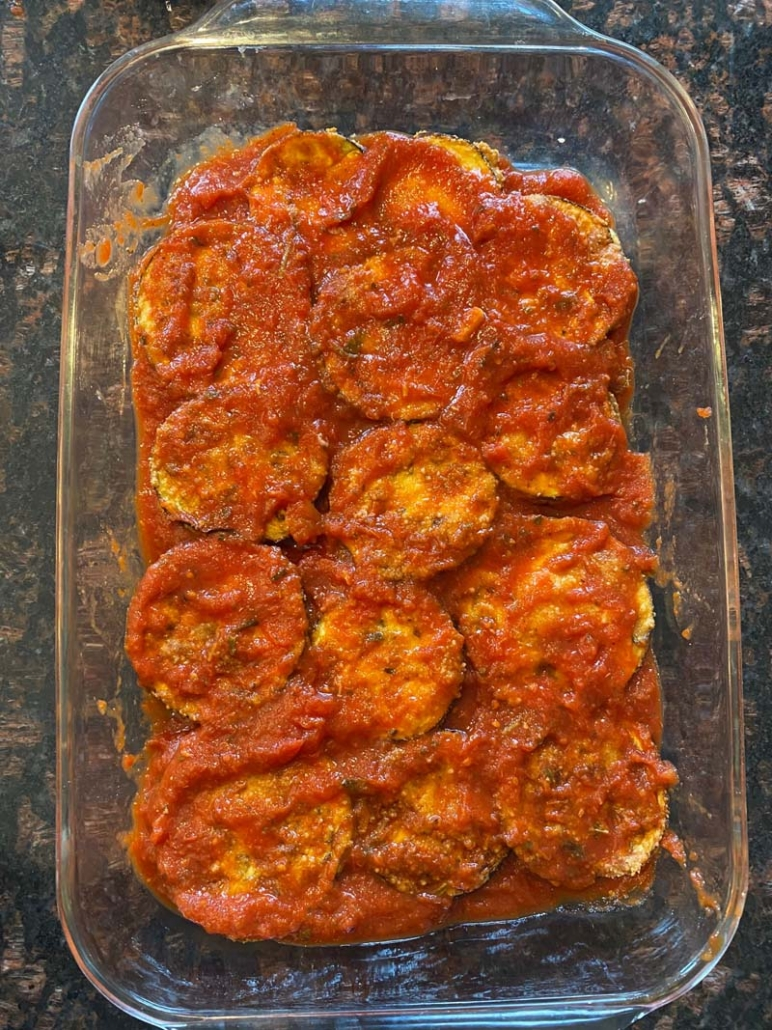 Spreading more marinara sauce on top of baked eggplant