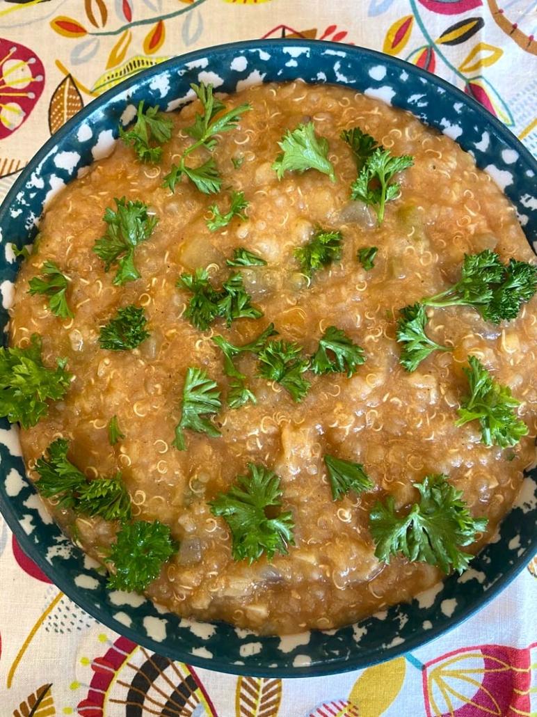 A bowl of Instant Pot Lentil Quinoa Soup with fresh chopped parsley