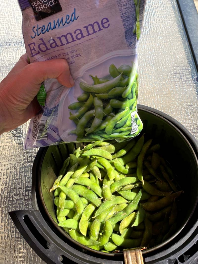 pouring bag of frozen edamame in the air fryer basket