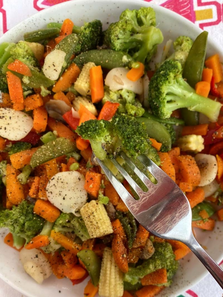 eating a bowl full of cooked veggies with a fork