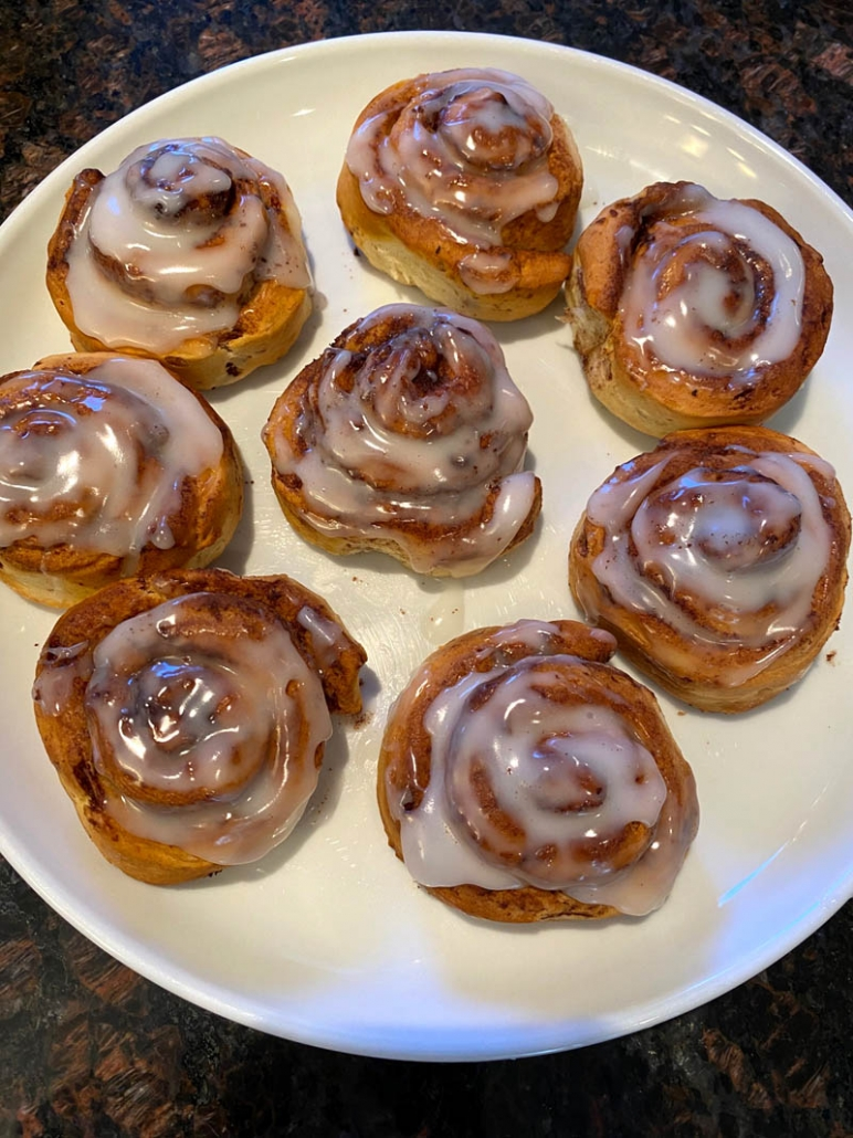 fluffy cinnamon rolls on a white plate with sugar icing