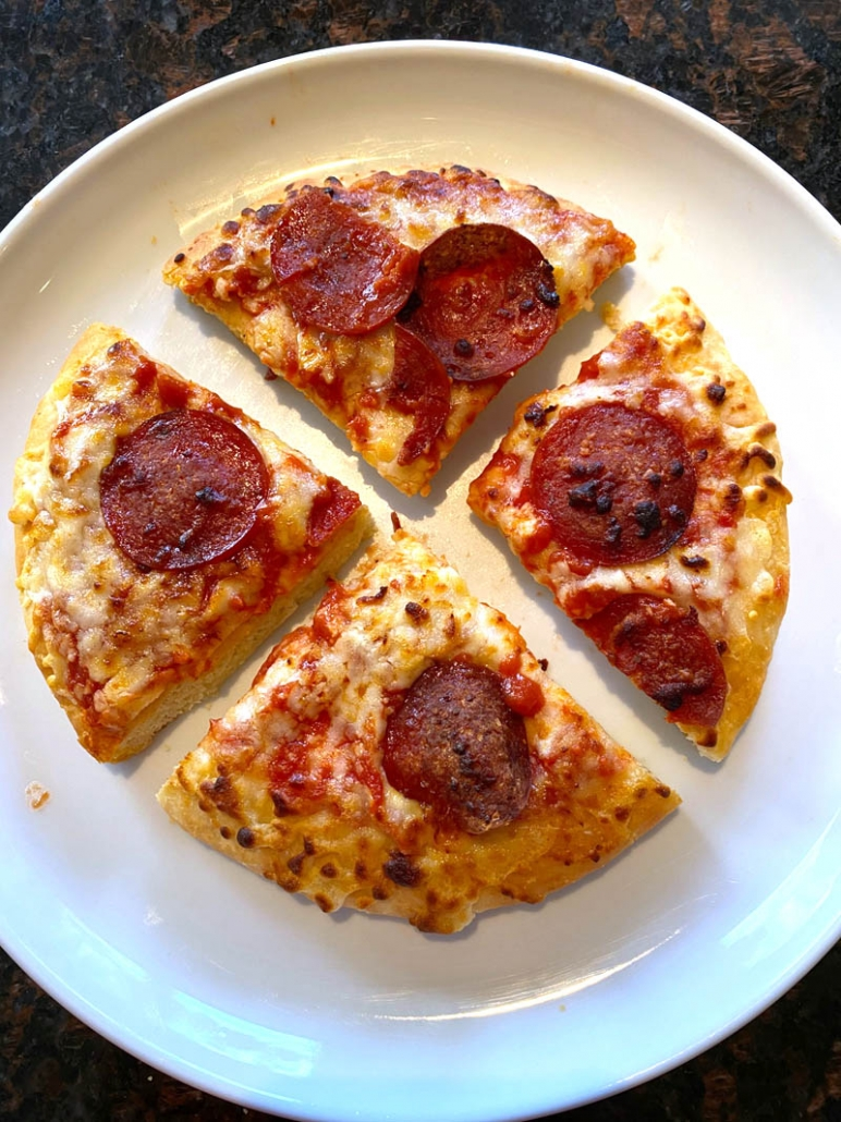 sliced personal pizza on a white plate