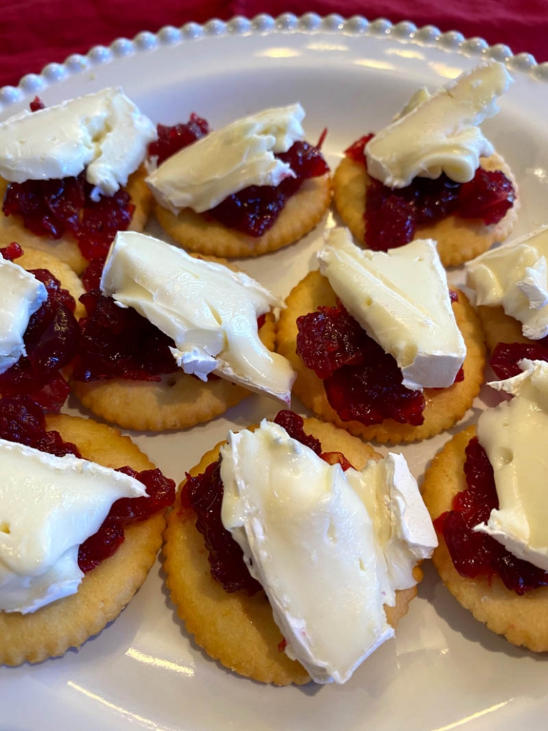 sliced brie and cranberry sauce on a ritz cracker