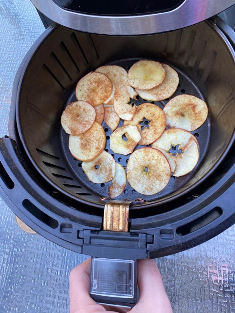 sprinkled cinnamon on apple slices in an air fryer basket