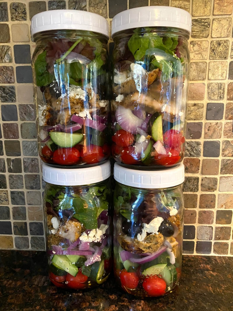 4 mason jars meal prepped with greek chicken salad