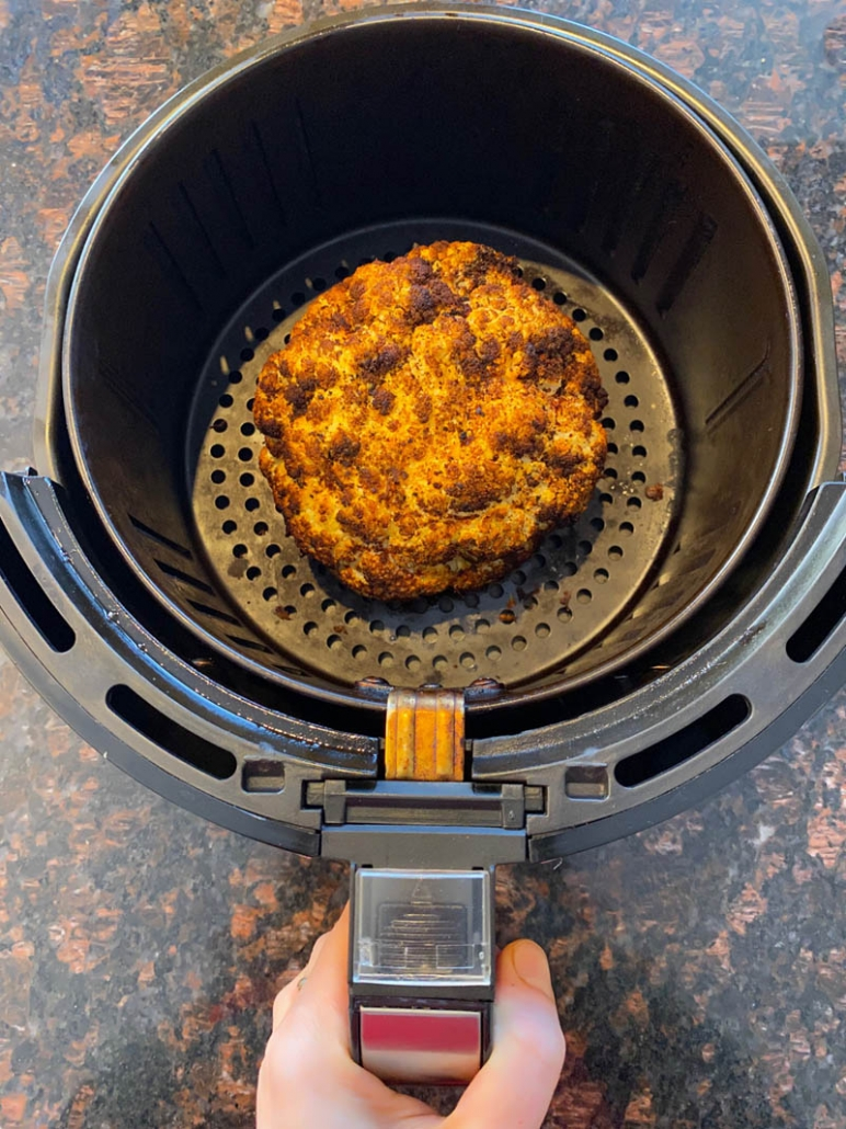 Pulling roasted cauliflower out of the air fryer