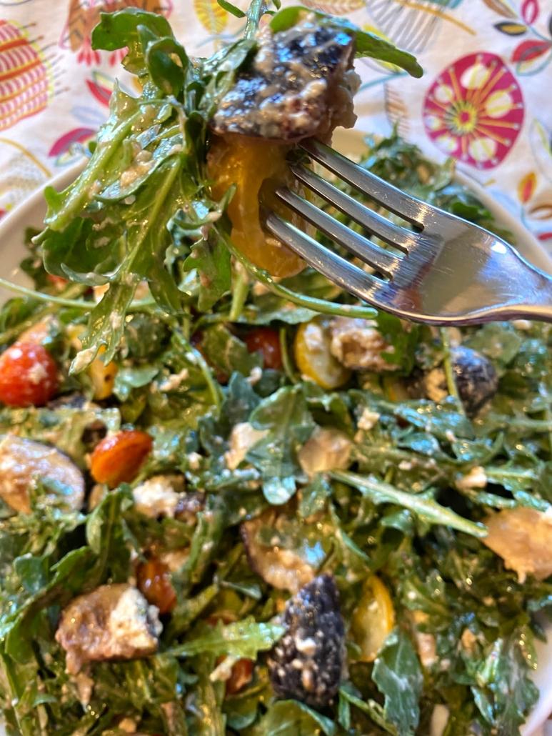 eating arugula burrata salad with a fork
