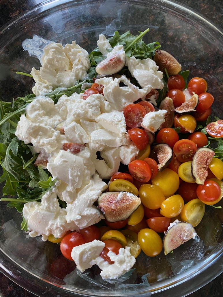 adding all of the ingredients for arugula burrata salad to a bowl