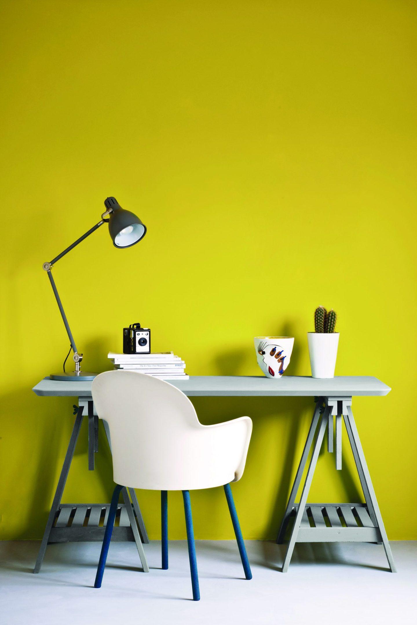 bir masa ve beyaz sandalye ile duvarda parlak sarı boya