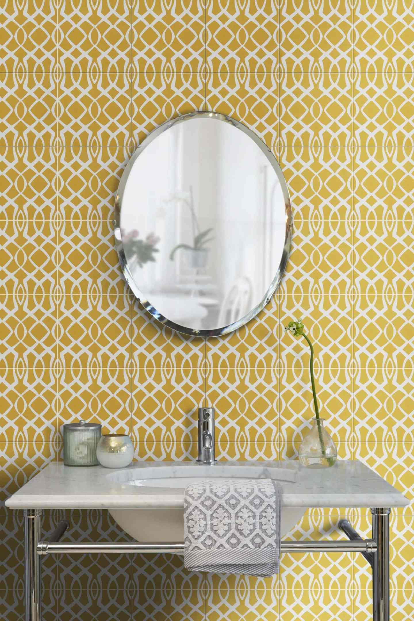 bright yellow geometric tiles in the bathroom with marble sink and oval mirror