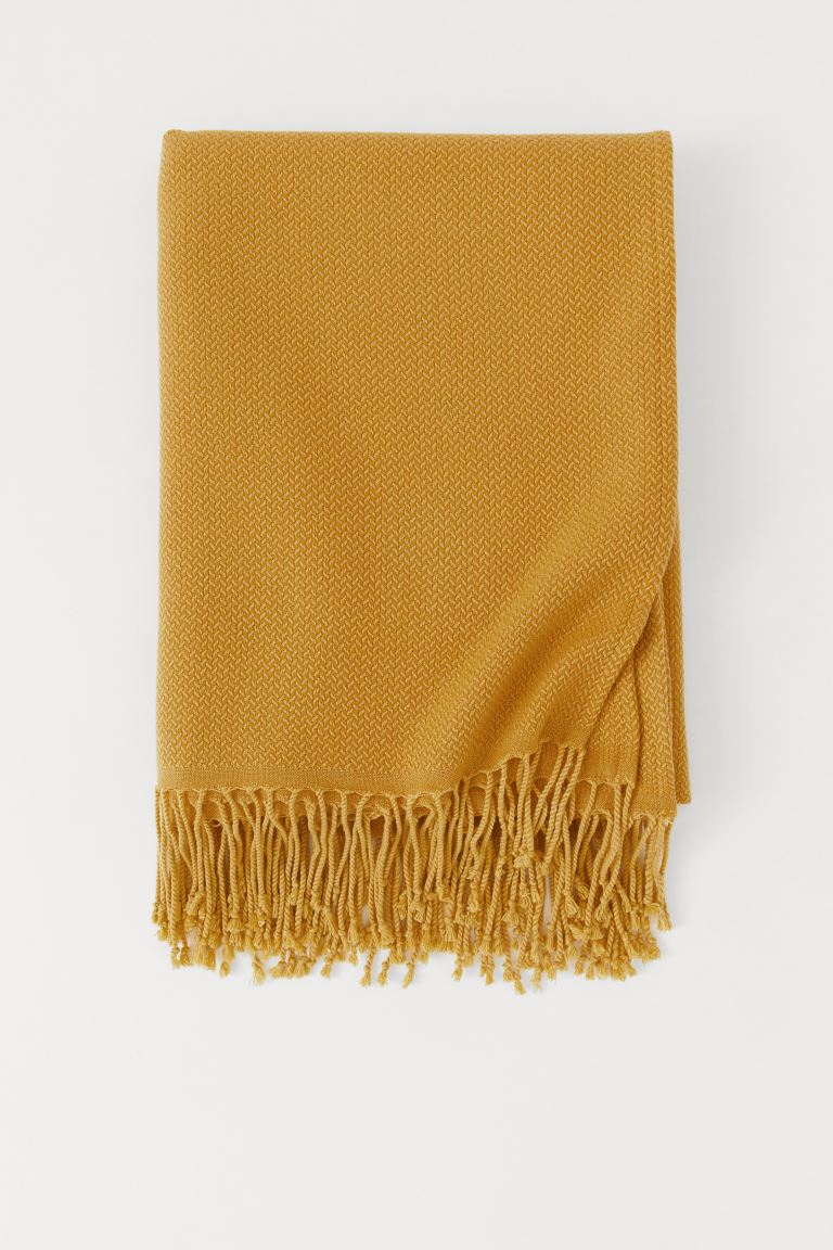 yellow knitted throw with tassels