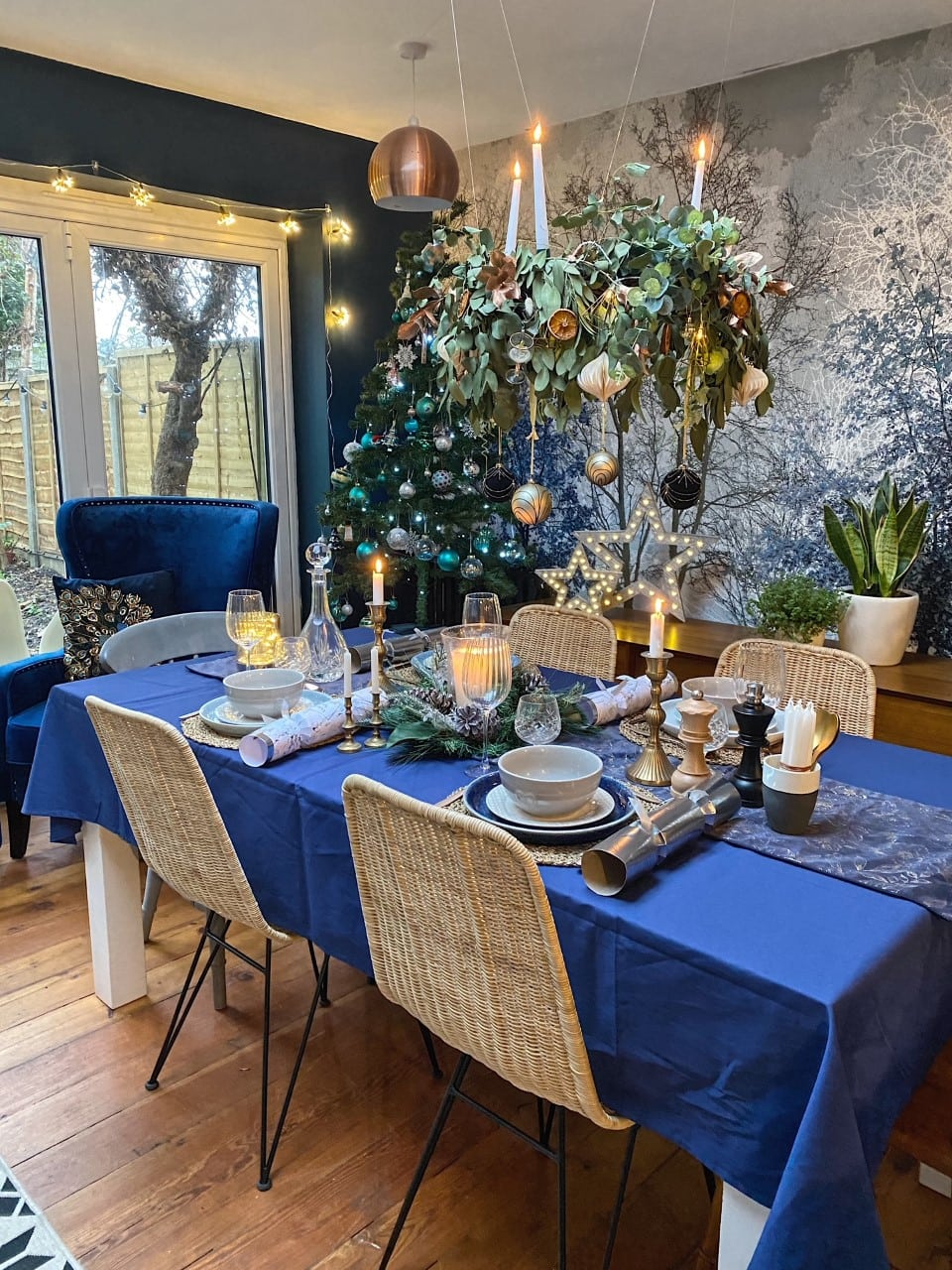 christmas table set up with wreath chandelier, candles and rattan chairs